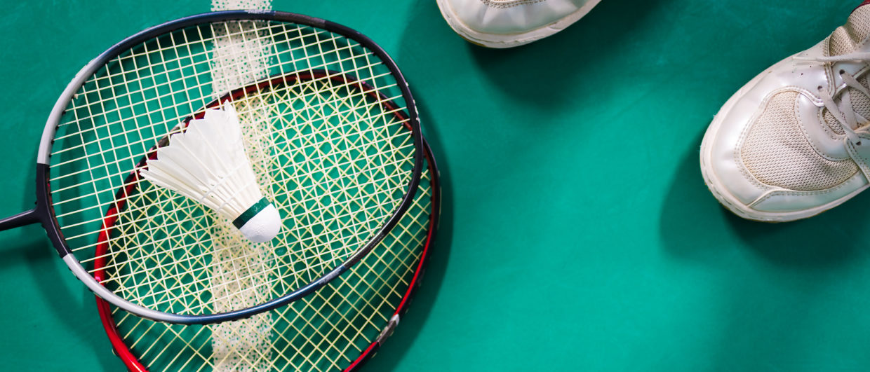 Badminton ball and racket on court floor.